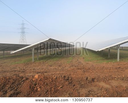 MANSFIELD WOODHOUSE ENGLAND - MARCH 13: Solar panels and nearby electricity pylon at a solar energy farm currently under construction. In Mansfield Woodhouse Nottinghamshire England. On 13th March 2016.