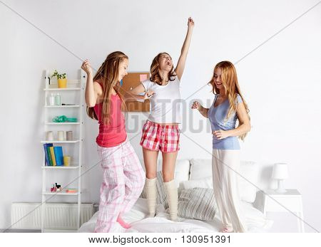 friendship, people and pajama party concept - happy friends or teenage girls having fun and jumping on bed at home