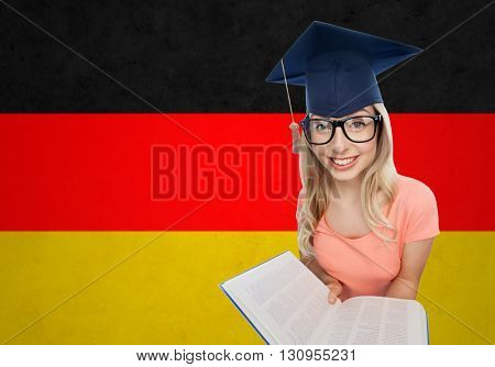 people, national education, knowledge and graduation concept - smiling young student woman in mortarboard and eyeglasses with encyclopedia book over german flag background