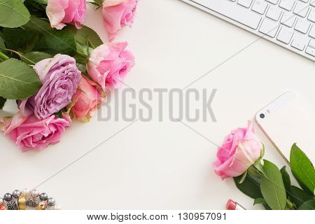 Styled flat desktop scene with mobile and flowers, copy space on white table