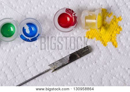 Closeup detail of colorful inks poured into small cups and tattoo needles isolated on white background