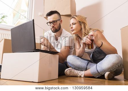 Young couple in love sitting on the floor of their new apartment planning redecoration and drinking juice