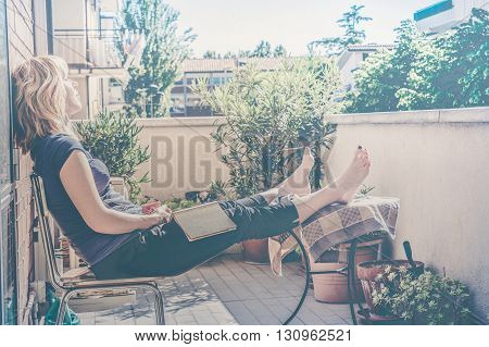 lazy woman on balcony falling asleep while reading a book - vintage color fading and sunny haze added