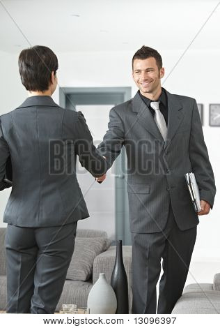 Business meeting at office lobby partners shaking hands.