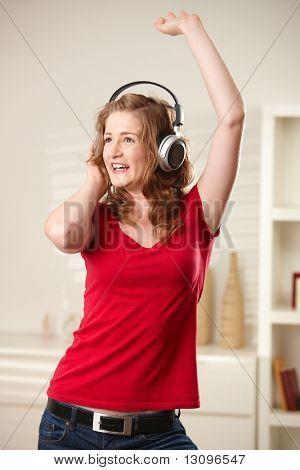 歌と踊りのヘッドフォンを家庭で幸せな十代の少女の笑みを浮かべてください。