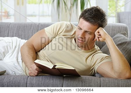 Handsome man in causal wear smiling lying on sofa reading handheld book.