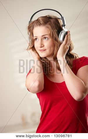 Portrait of happy teen girl listening to music holding onto headphones looking up.