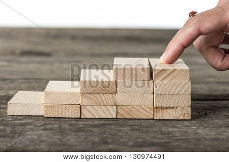 Staircase made of wooden pegs with male finger on top with a ladybug on it representing a way to success.