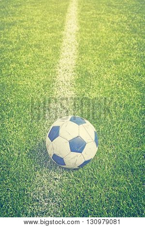 Retro Toned Used Soccer Ball On Grass By Sideline.