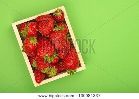 Strawberry In Wooden Box Over Green