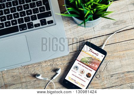 Travel booking website in a smart phone screen. Office wooden desktop.