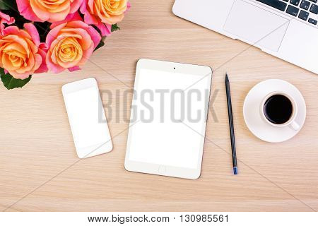 Top view of creative woman's desktop with roses blank white smart phone and tablet screens coffee cup pencil and laptop keyboard. Mock up