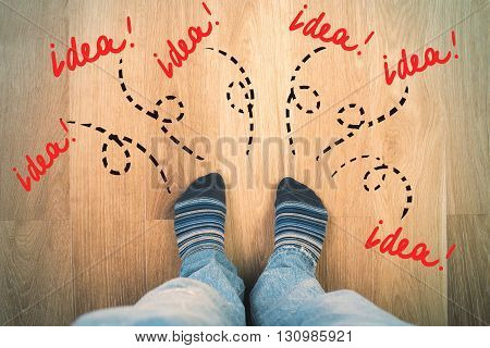 Top view of male legs and feet in socks on wooden floor with sketches around. Idea concept