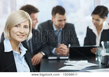 Portrait of mid-adult businesswoman smiling at camera with colleagues at meeting in background,