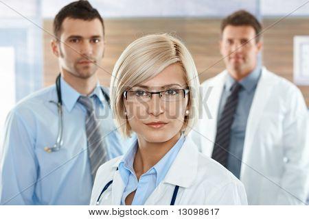 Equipo médico en el hospital corredor doctora frente mirando a cámara, sonriendo.