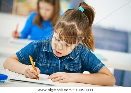 Young girl writing at school sitting in class with other girl in background.