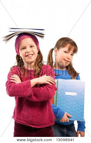 Schoolgirls posing with exercise books, girl balancing books on top of head, other holding in arm.