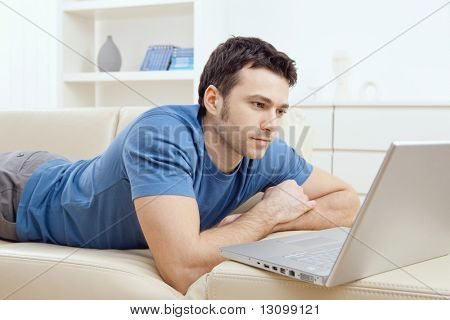 Young man laying on sofa and using laptop at home.