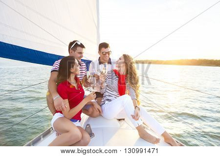 Smiling friends sitting on yacht deck and greeting drinking champagne. Travel and vacation concept