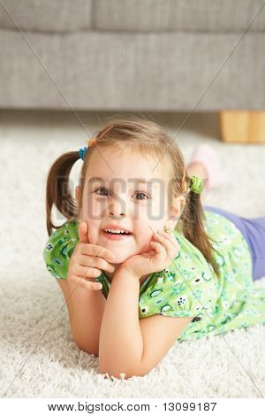 Portrait of happy little girl lying on floor at home looking at camera, smiling.
