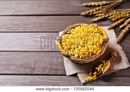 Dried pasta cavatappi in a basket on a wooden background. Selective focus.