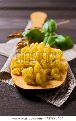 Dried pasta cavatappi in a spoon on a wooden background. Selective focus.