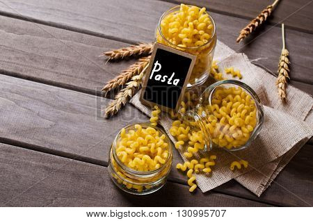 Dried pasta cavatappi in the glass on a wooden background. Selective focus.