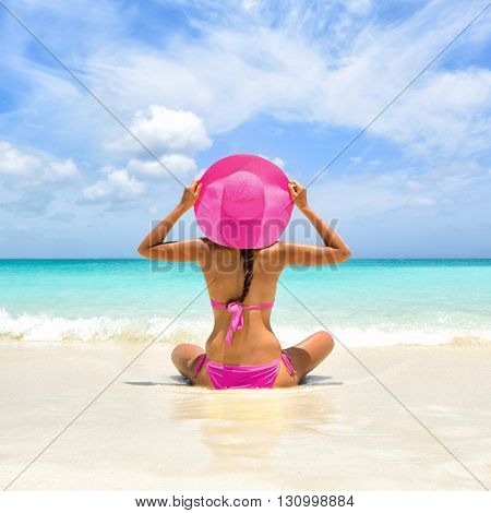 Perfect paradise summer vacation happiness carefree happy woman relaxing sitting in sand enjoying tropical beach destination. Back view of bikini girl holding pink straw hat on Caribbean holiday.