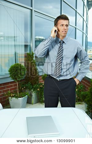 Serious businessman standing outdoor talking on mobile phone, looking away.