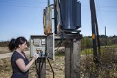 Electrician engineer woman checking electricity meter and invoice standing near electricity switchgear power transformer substation outdoors. poster