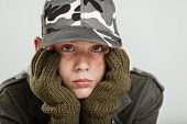 Young boy in jacket brown gloves and gray camouflage hat holding his pouting face in hands poster