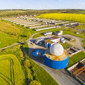 Aerial view to biogas plant from pig farm in rapeseed fields. Renewable energy from biomass. Modern agriculture in Czech Republic and European Union.  poster