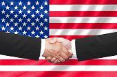 two businessmen shakehand over american national flag poster