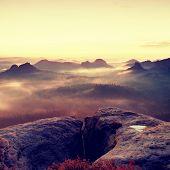 Fantastic dreamy sunrise on the top of the rocky mountain with the view into misty valley poster