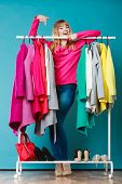 Happy smiling pretty woman choosing clothes to wear in wardrobe. Gorgeous young girl customer shopping in mall shop. Fashion clothing sale concept. poster