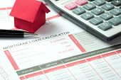 Mortgage loan balance sheet with a miniature ed paper house and calculator poster