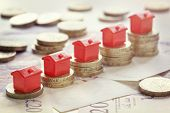 Minature houses resting on pound coin stacks concept for property ladder, mortgage and real estate investment poster