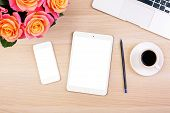 Top view of creative woman's desktop with roses blank white smart phone and tablet screens coffee cup pencil and laptop keyboard. Mock up poster
