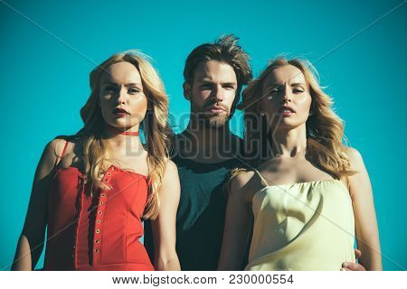 Twins Women With Macho On Blue Sky Background. Family Trust, Polygamy, Betrayal, Swinger. Love Trian