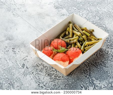 Boiled String Beans And Fish Balls In Sauce In A Lunchbox On A Gray Background. Healthy Food Deliver