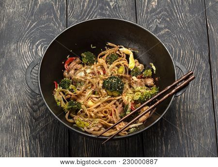 Asian Dish Of Meat, Vegetables And Noodles With Spices In Wok, On Background Of Wooden Table