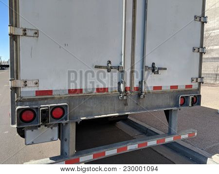 Rear Doors Of Long Haul Trailer; Red Signal Lights And Bumper With Red-white Sticker