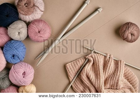 Set Of Colorful Wool Yarn And Knitting On Knitting Needles On Beige Background. Knitting As A Kind O