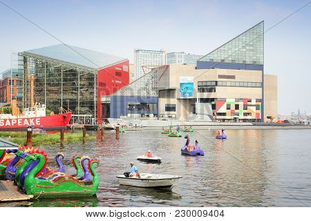 Baltimore, Usa - June 12, 2013: People Ride Dragon Paddleboats With National Aquarium In Background