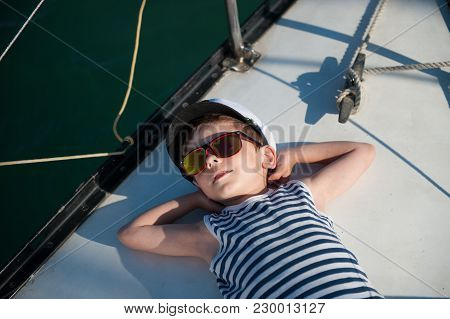 Handsome Little Kid In Sunglasses Lying On Board Of White Yacht Enjoying