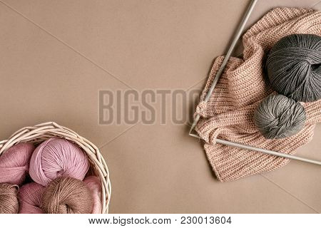 Balls Of Merino Wool Yarn, Knitting On Knitting Needles On A Beige Surface. Pink, White And Gray Bal