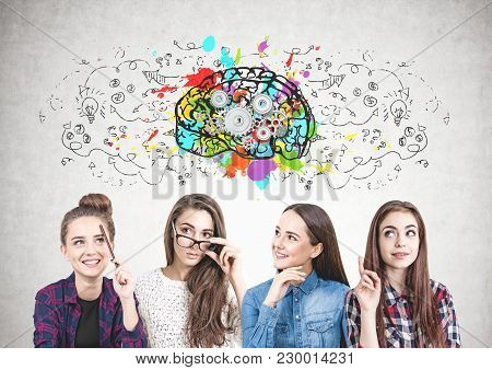 Four Teen Girls In Casual And Formal Clothes Are Standing Together And Brainstorming. A Concrete Wal
