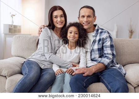 Happy Family. Pretty Joyful Curly-haired Girl Smiling And Sitting On The Couch With Her Parents And