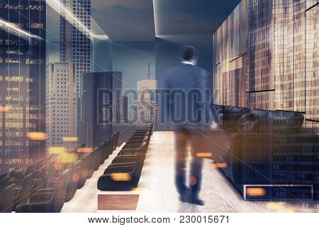African American Businessman In A Modern Cinema Interior With Dark And Wooden Walls, A Wooden Floor,