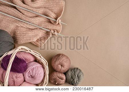 Balls Of Merino Wool Yarn, Knitting On Knitting Needles On A Beige Surface. Pink, Gray And Purple Ba